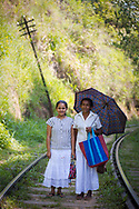 A mother and her adult daughter walk down the train tracks in Ella, one of Sri Lanka's most popular tourist destinations.