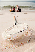 A net sits on the beach as a young girl and boy play in the sand with their grandmother.