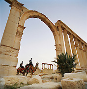 Men ride camels in the early morning at the Roman ruins in the ancient city of Palmyra, Syria