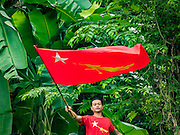 09 NOVEMBER 2015 - YANGON, MYANMAR:   A man waves a NLD flag in a field across the street from NLD headquaters. Thousands of National League for Democracy (NLD) supporters gathered at NLD headquarters on Shwegondaing Road in central Yangon to celebrate their apparent landslide victory in Myanmar's national elections that took place Sunday. The announcement of official results was delayed repeatedly Monday, but early reports are that the NLD did very well against the incumbent USDP.   PHOTO BY JACK KURTZ