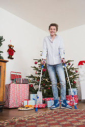Portrait of teenage boy standing with crutches against Christmas tree