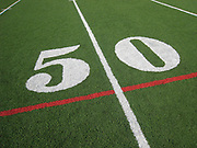 Close up angled photo of a fifty on a football field indicating the fifty yard line