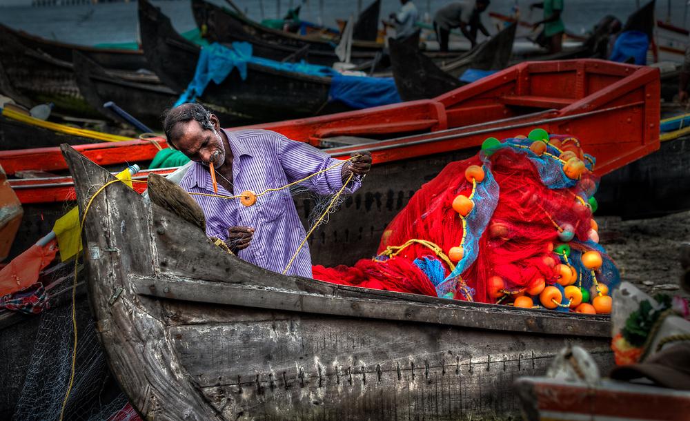 Fisherman repairing his nets in India
