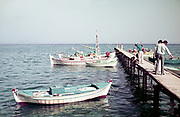 Tourists by the coast on pier looking at fishing boat, Kos, Greece 1970s
