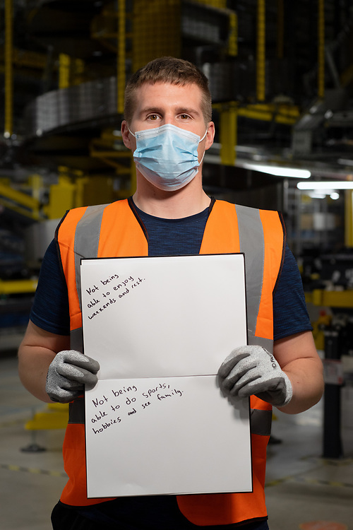 Romans Tjabuts  is pictured inside Amazon Fulfillment Center Man 3 Near Bolton.  He has worked at Amazon for 8  months, he is from Latvia but moved to England aged 11. He was asked to write two ways he felt the COVID 19 Lockdown had impacted himself.