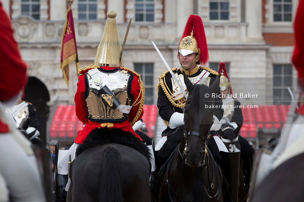 Members of the The Queen's Life Guard (red tunics) and the Blues and Royals (blue tunics) change the guard during the daily ceremonial in Horse Guards Parade, on 11th June 2019, in London, England. Life Guards have stood guard at Horse Guards, the official entrance to St James and Buckingham Palace, since the Restoration of King Charles II in 1660.