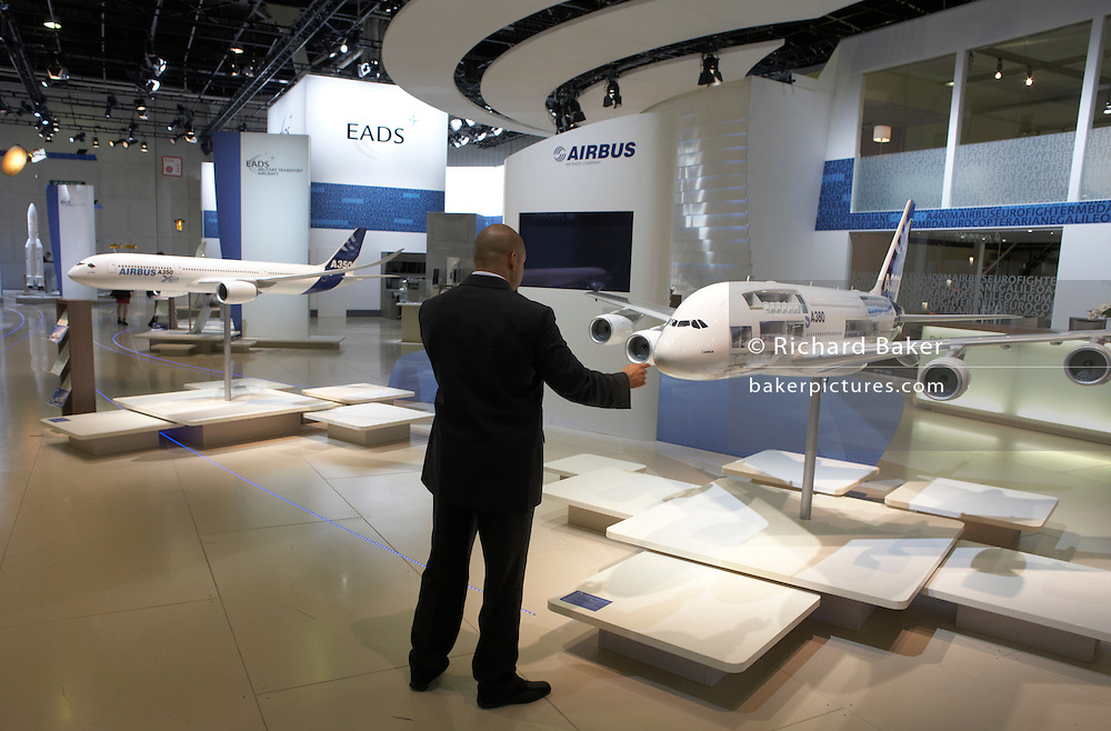 Man touches scale model of A380 airliner displayed at the Airbus/EADS stand during the Paris Air Show exhibition at Le Bourget
