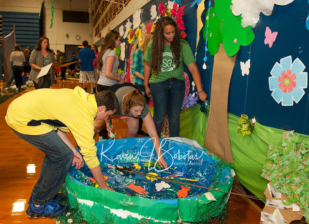 """Spring"" is in the air for Freshman Anthony Gentile, Lauren Camella and Chloe Bourgeois as they the pond in their hallway on Thursday evening in preparation for Gilford High School's Homecoming festivities.   (Karen Bobotas/for the Laconia Daily Sun)"