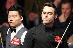 Ronnie O'Sullivan reacts after a shot during his match against Ding Junhui (left), on day twelve of the Betfred Snooker World Championships at the Crucible Theatre, Sheffield.