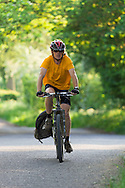 Cyclist on leafy lane on the way into Bradbourne village, Derbyshire