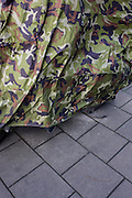 Motorbike covered with nature camouflage on urban street.