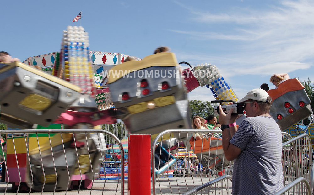 New Paltz, NY - A man uses a camcorder at a ride at the Ulster County Fair on Aug. 3, 2008.