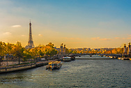 Golden glow of the morning sun on the Siene and Eiffel Tower on an clear Autumn day.