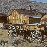 An old wagon stands near abandoned houses and buildings at California's Bodie Ghost Town State Park.