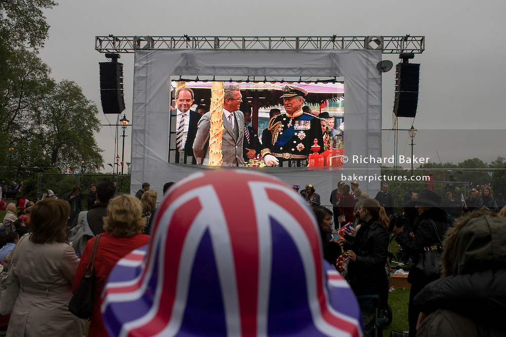 Watching giant TV screen coverage, the great British public brave bad weather to celebrate the Queen's Diamond Jubilee flotilla on the river Thames. 1,000 boats made their way past Battersea Park, London including their reigning monarch of 60 years and other members of the royal family during a weekend of official festivities and street parties.
