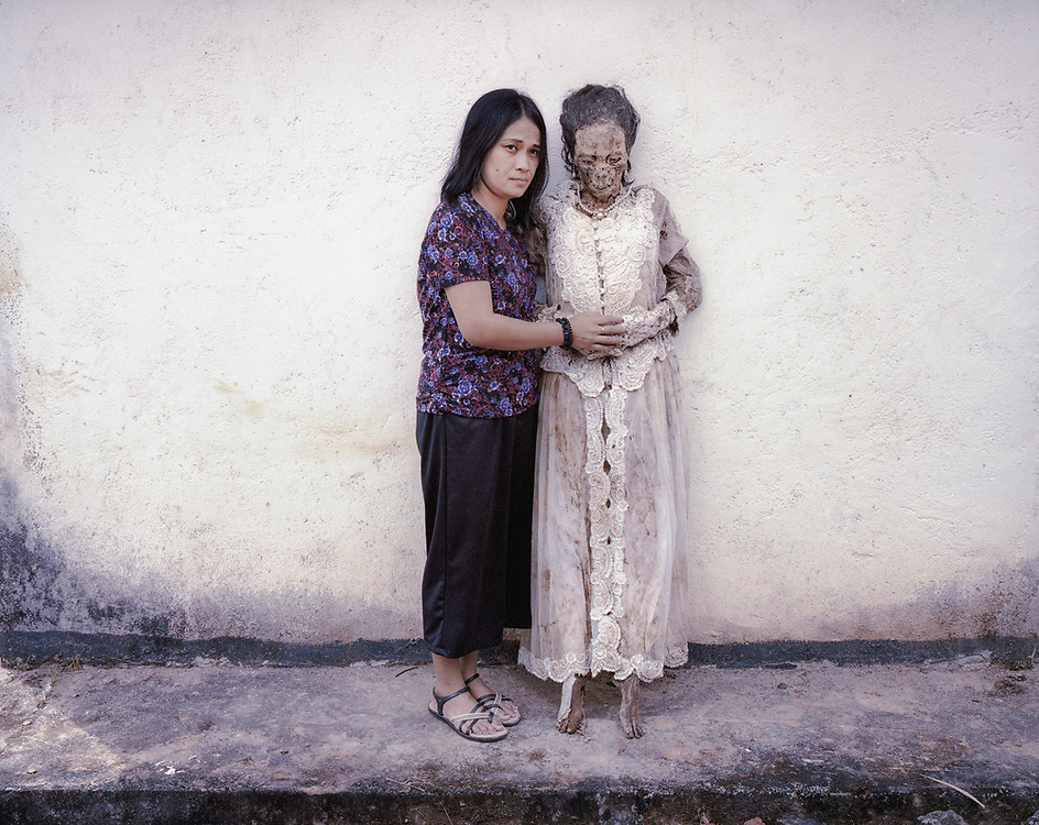 Abigael Randa (37) and her mother, Lince Bunga, who died in 2015 at age 58. This is the first time Lince's body was taken out since her death.  It is customary not to visibly cry during Ma'nene and Abigael went to the back to shed tears. <br /> <br /> Ma'nene is a tradition that takes place in August after harvest where the bodies of the dead loved ones are exhumed to be cleaned, groomed and dressed. For most, it's a bittersweet moment, a chance to reunite and physically see and touch and reconnect with loved ones who had passed on.