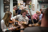 Local residents playing during a music session at the Colonsay Hotel on the the Inner Hebridean island of Colonsay on Scotland's west coast.  The island is in the council area of Argyll and Bute and has an area of 4,074 hectares (15.7 sq mi). Aligned on a south-west to north-east axis, it measures 8 miles (13 km) in length and reaches 3 miles (4.8 km) at its widest point, in 2019 it had a permanent population of 136 adults and children.