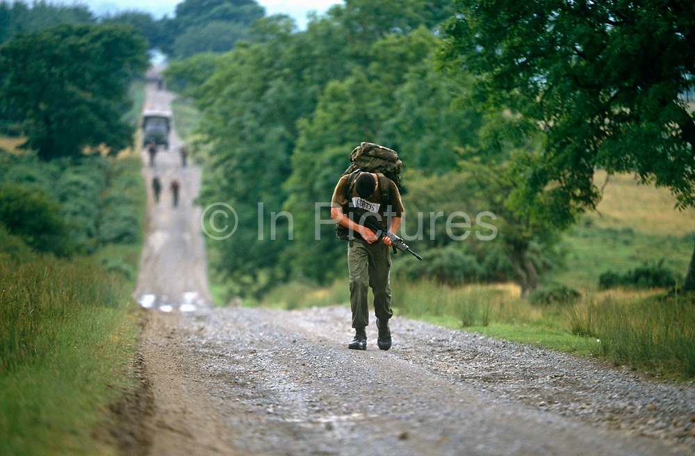 A boy soldier is about to collapse on the ground suffering fatigue and dehydration on the rigorous long march conducted as a squad, over undulating terrain with each candidate carrying a Bergen (backpack) weighing 35 pounds (plus water) and a weapon. The lad is buckling under the weight of his backpack and weapon carried on a hot day and without drinking enough fluids. The 10-mile march must be completed in 1 hour and 50 minutes and it forms part of the 14-week long Pegasus (P) Company selection programme that recruits wanting to join the British Army's elite Parachute Regiment, held regularly at Catterick army barracks in Yorkshire, need to pass (with other tests) before earning the right to wear the esteemed maroon beret.
