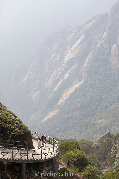 Aerial view of two hikers walking along a footpath in mountains leaving the Jade Screen Pavilion, Huangshan Mountain Range, Anhui Province, China