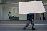 An obscured workman manhandles a wooden board sheeting past an art gallery window where a receptionist works at a computer, on 5th March 2019, in London, England.