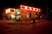 Night street scene in De Hui city, Jilin Province. North Eastern China. Restaurants and transport and neon signs.