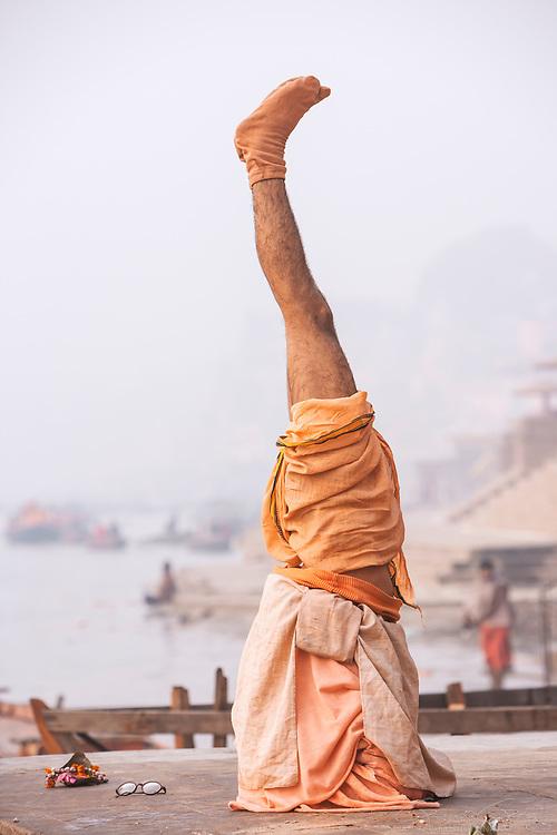 A Hindu Sadhu performing a headstand during his morning yoga and meditation routine, River Ganges, Varanasi, India