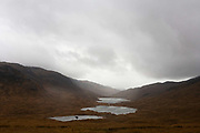 An empty landscape of distant tree and moorland waters on Glen More, Isle of Mull, Scotland.Back on the main A849 road that routes through the valley of Glen More, a 6-mile-diameter crater of an extinct volcano.
