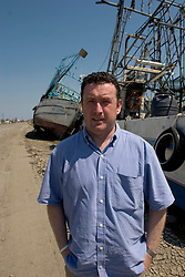 08 Sept 2005. New Orleans, Louisiana. Hurricane Katrina aftermath. <br /> The Daily Mirror's Aidan McGurran in East New Orleans, where the tidal surge washed over the land and devastated homes and property dumping ships on the Chef Menteur highway.<br /> Photo; ©Charlie Varley/varleypix.com