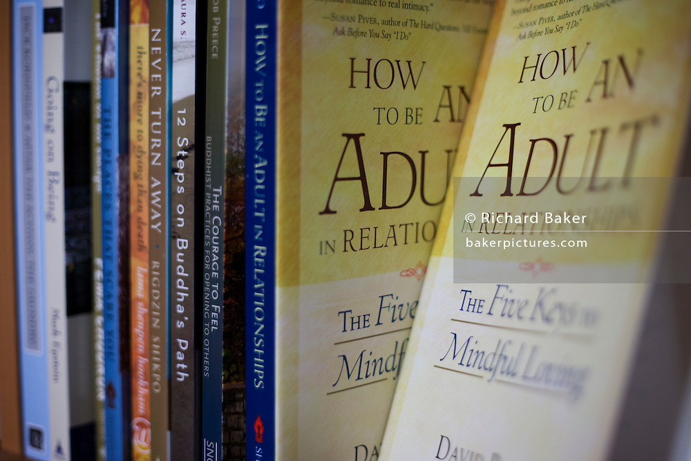 Book covers and spines on shelf at the Rivendell Buddhist Retreat Centre, East Sussex, England.