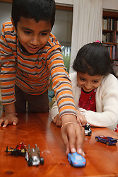 Asian children playing with toy cars