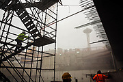 Workers climb scaffolding at the site as Bertha, the world's largest tunnel boring machine, finally breaks through the north end of the Seattle waterfront tunnel, Tuesday afternoon, April 4, 2017.
