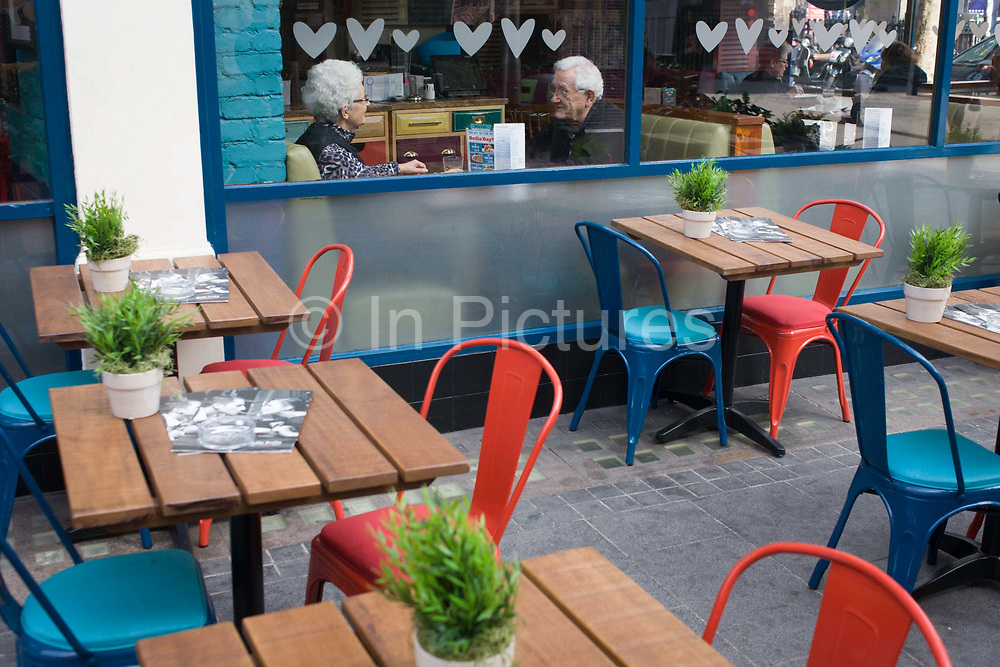 An elderly couple sit in a central London cafe with love hearts theme stencils. The romantic couple are seated in the window as they talk to each other across their table inside. We look across other tables and chairs with red and blue theme complimentary colours on the spectrum. Empty places take our attention to the pensioner lovers in a scene of romance, relationships and perhaps marriage too.