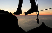 Balancing on a slackline 150m long spanning a ravine on Table Mountain, Warren Gans from Cape Town walks the line at sunset, 1,085m above sea level below. Picture by Greg Beadle