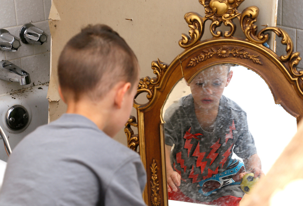 Timothy Stephan, 3, reflected in a mud-stained mirror finds one of his toy balls in his tornado-destroyed home on 6th Avenue in Moore, Oklahoma May 23, 2013. The tornado was the strongest in the United States in nearly two years and cut a path of destruction 17 miles long and 1.3 miles wide. REUTERS/Rick Wilking (UNITED STATES)