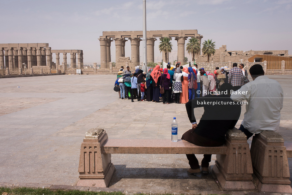 A party of schoolgirls gather to look at tourist trinkets in the main square in front of the ancient Egyptian columns of Luxor Temple, Luxor, Nile Valley, Egypt. The temple behind was built by Amenhotep III, completed by Tutankhamun then added to by Rameses II. Towards the rear is a granite shrine dedicated to Alexander the Great and in another part, was a Roman encampment. The temple has been in almost continuous use as a place of worship right up to the present day.