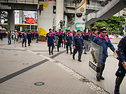 "14 JULY 2013 - BANGKOK, THAILAND:  Thai riot police head walk across the plaza in front of the Bangkok Arts and Culture Centre after about 150 members of the so called ""White Mask"" movement marched through the central shopping district of Bangkok Sunday to call for the resignation of Yingluck Shinawatra, the Prime Minister of Thailand. The White Mask protesters are strong supporters of the Thai monarchy. They claim that Yingluck is acting as a puppet for her brother, former Prime Minister Thaksin Shinawatra, who was deposed by a military coup in 2006 and now lives in exile in Dubai.       PHOTO BY JACK KURTZ"