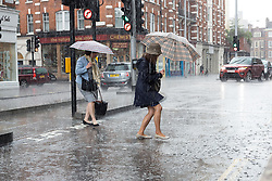 © Licensed to London News Pictures. 13/05/2014. London, UK. Two women with umbrellas are seen in a sudden and brief heavy downpour of rain in Kings Road, London on 13 May 2014. Photo credit : Vickie Flores/LNP