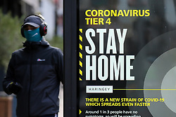 © Licensed to London News Pictures. 30/12/2020. London, UK. A man wearing a face covering walks past the government's 'Coronavirus Tier 4 - Stay Home' publicity poster in north London, as the Medicines and Healthcare Products Regulatory Agency (MHRA) approves the Oxford/AstraZeneca vaccine (codenamed AZD1222 or ChAdOx1) for use in the UK. Health Secretary Matt Hancock has said that the vaccine will be rolled out from 4 January 2021. A number of cities will be put into tougher Tier 4 COVID-19 restrictions after the mutated SARS-Cov-2 virus continues to spread around the country and coronavirus infection rates rise. Photo credit: Dinendra Haria/LNP