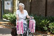 Een oudere vrouw fietst met haar boodschappen aan het stuur door Goirle.<br /> <br /> An older woman cycling with her shopping by Goirle.