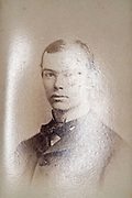 reflection on the photo surface of a head and shoulder portrait of a young adult man