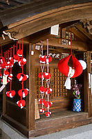 A sarubobo is a Japanese amulet, particularly associated with the town of Takayama in Gifu prefecture. Sarubobos are red human shaped dolls with no facial features, made in a variety of sizes. Traditionally, sarubobos are made by grandmothers for their grandchildren as dolls, and for their daughters as a charm for good marriage, children and to ensure a well rounded marriage.  Sarubobo dolls and charms usually have no facial features.  One suggestion is that the absence of a face allows the owner to imagine it.  When the owner is sad, they can imagine their sarubobo to be sad too.