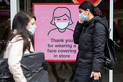 © Licensed to London News Pictures. 16/10/2020. Manchester, UK. People wearing face masks walk past a sign in a shop window on Market Street, Manchester, reminding customers to wear a mask. Manchester is on the verge of a Tier 3 lockdown. Photo credit: Kerry Elsworth/LNP