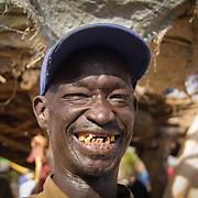 The toothy grin of a fried mutton vendor at the Sunday market near Koumbadiouma. Kolda, Senegal.