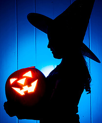 EDITORS PLEASE NOTE orange and blue gels were used to create this image. PICTURE POSED BY MODEL A young girl with a pumpkin as she prepares for Halloween.