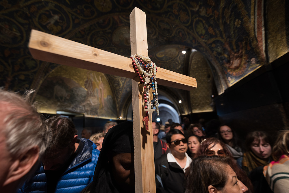19 April 2019, Jerusalem: A woman prays holding a wooden cross, in the Church of the Holy Sepulchre. Thousands of Christians march the Via Dolorosa on Good Friday, marking the stations of the cross in the Jerusalem Old City, in memory of the path Jesus walked carrying his cross towards his crucifixion.