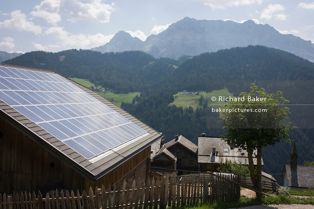 Solar panels on the roof of a Dolomites farm's barn roof in the old rural hamlet of Aireië, near Wengen-La Val, in south Tyrol, Italy.