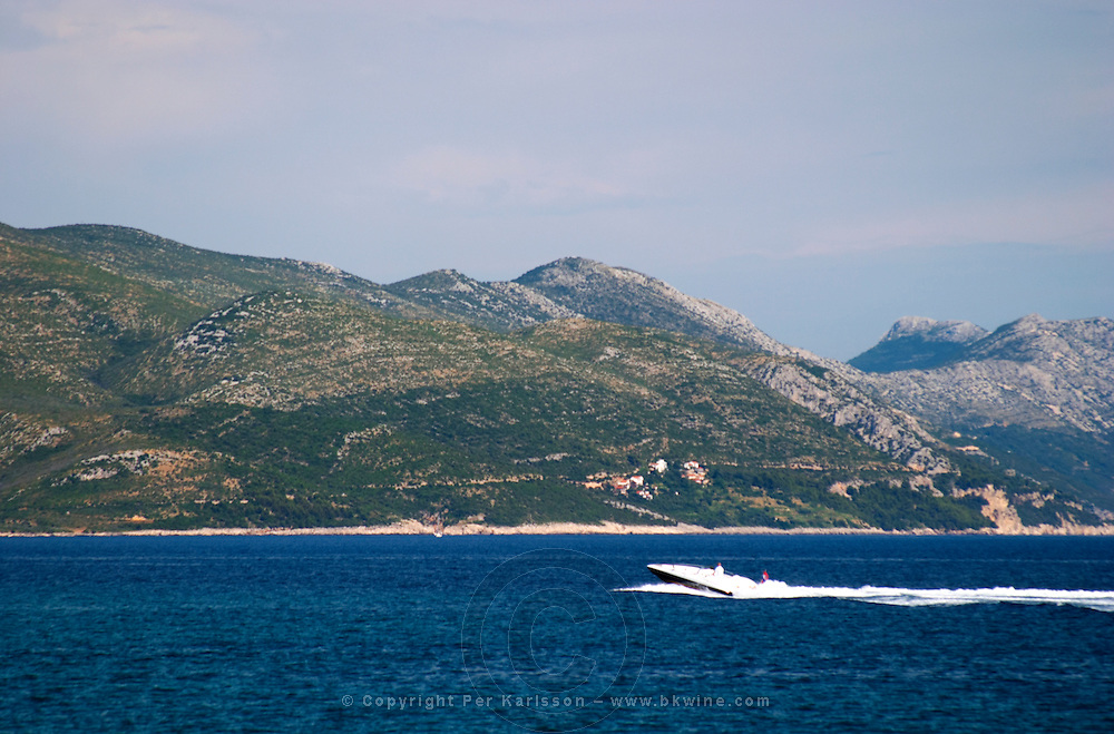 A speed boat speedboat on the blue sea and the massive mountains in the background. Mount Sveti Ilija mountain. Orebic town, holiday resort on the south coast of the Peljesac peninsula. Orebic town. Peljesac peninsula. Dalmatian Coast, Croatia, Europe.