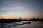 Sunset along the river Thames looking towards inner London from the East. in the distance The Shard can be seen under construction and in the foreground, Thames Clipper public transport boats glide along in silhouette.