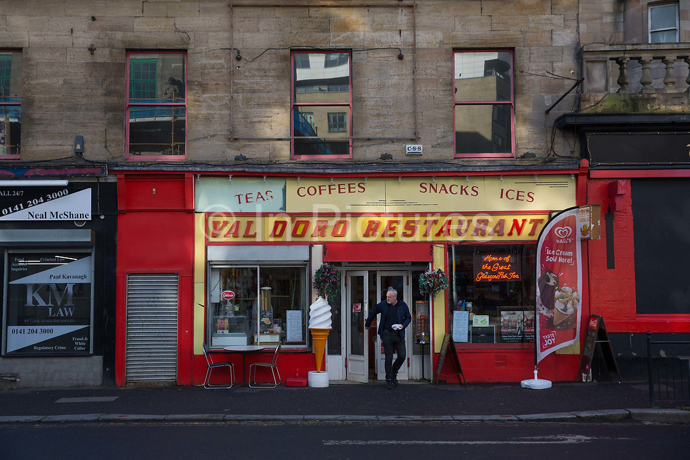 A man with a take away walks out of Val DOro Restaurant on the 2nd November 2018 in Glasgow in the United Kingdom. Val DOro is the oldest fish and chip shop in Glasgow dating back to 1875.