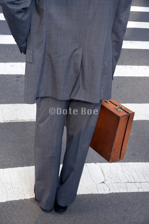 business man with leather briefcase waiting to cross the street